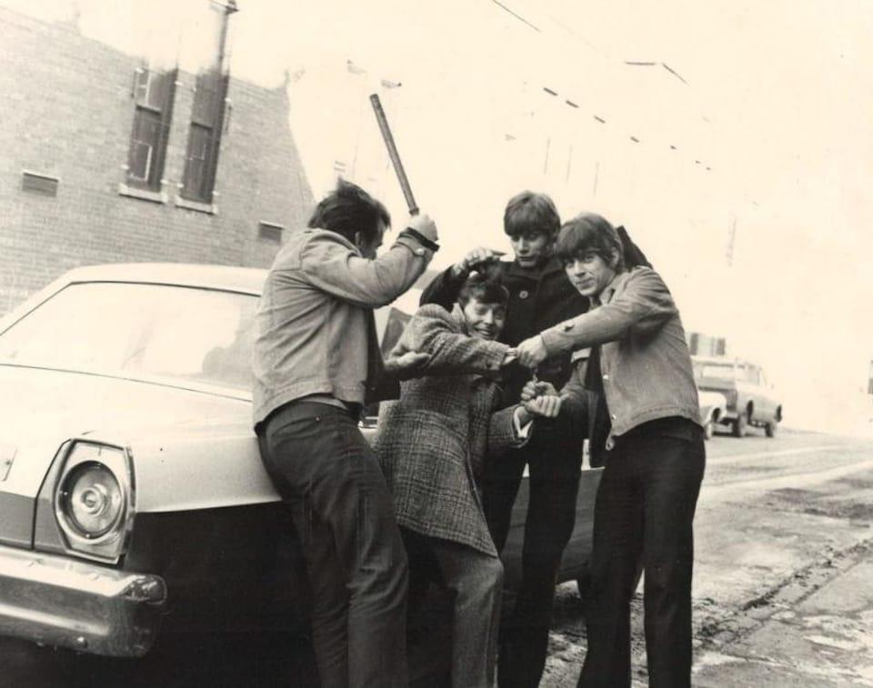 Les Loups Blancs font les fanfarons près d'un véhicule de la Sûreté du Québec avec une matraque à la main! Paul Daraîche est à droite, Maurice Bastien est au centre, avec le manteau noir.