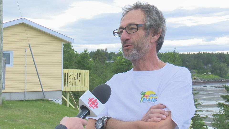 Un homme se trouve à l'extérieur sur un terrain de gazon. Il se fait interviewer par une journaliste de Radio-Canada. On remarque un bout du fleuve Saint-Laurent derrière l'homme. Il s'agit de Luc Meyer.
