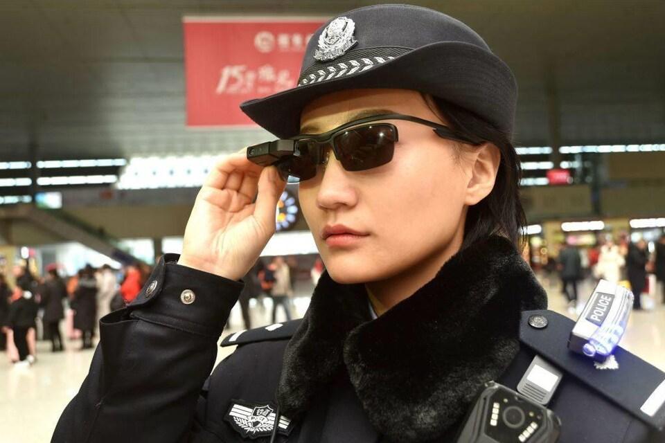 Une policière touche ses lunettes fumées de haute technologie dans une gare de train.