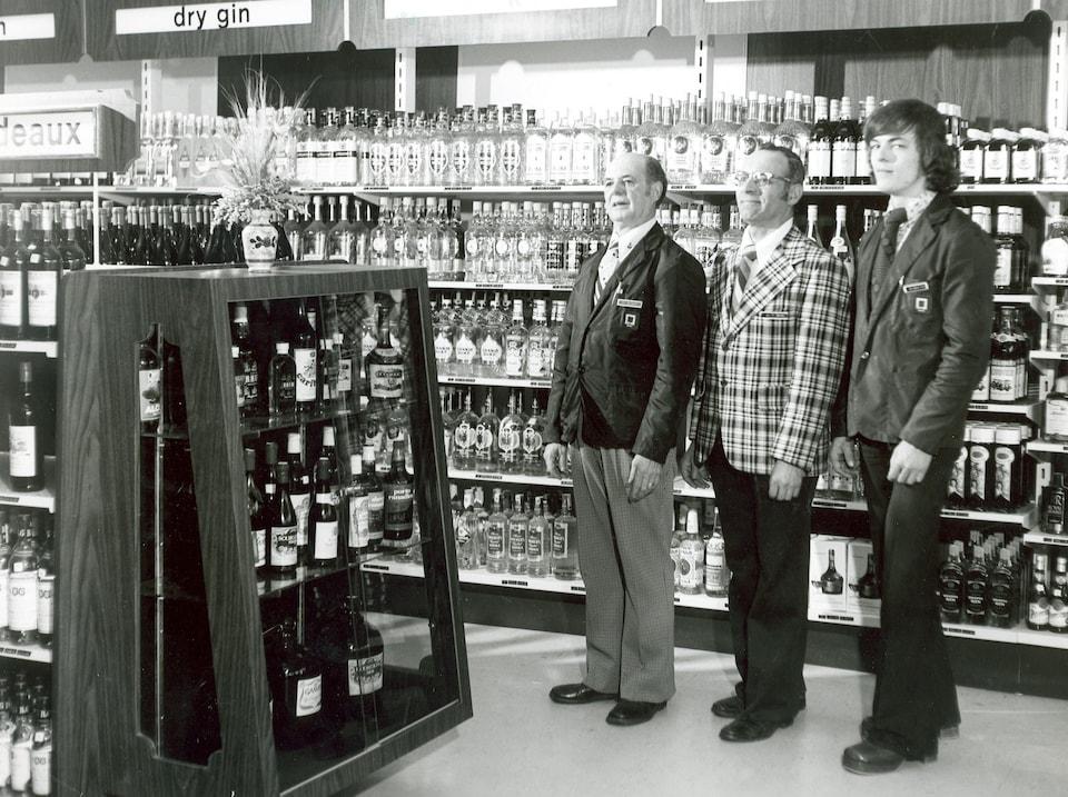 Trois hommes devant des rayons remplis de bouteilles d'alcool