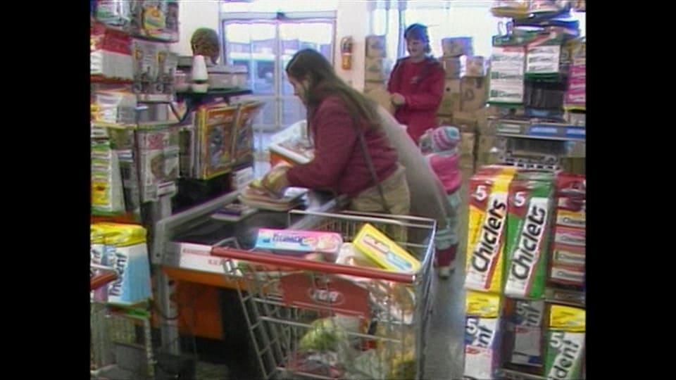Une image d'archives des années 1980 dans un commerce. Une dame est à la caisse.
