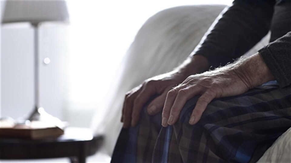 Un homme âgé assis sur son lit, avec les mains sur ses genoux.