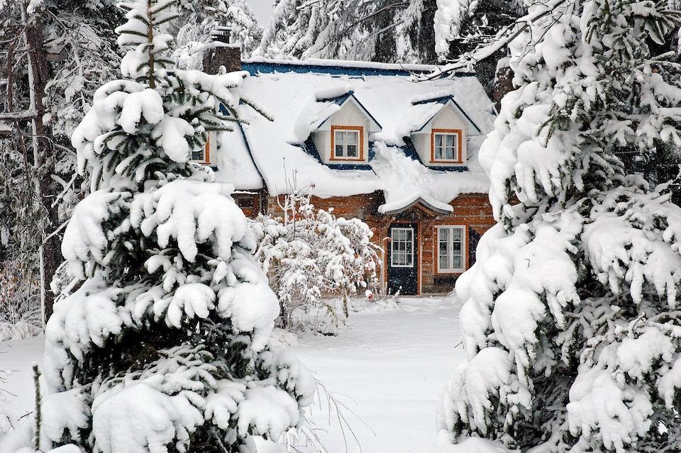 Une jolie maison dans la forêt enneigée.