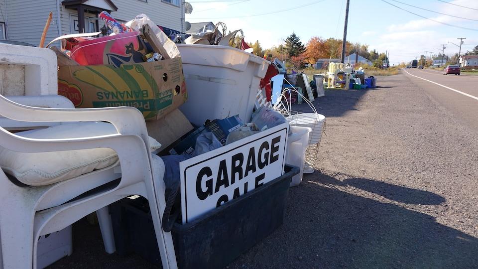 Divers objets sur le bord de la route avec une pancarte où on peut lire «garage sale», ou vente de garage en français.