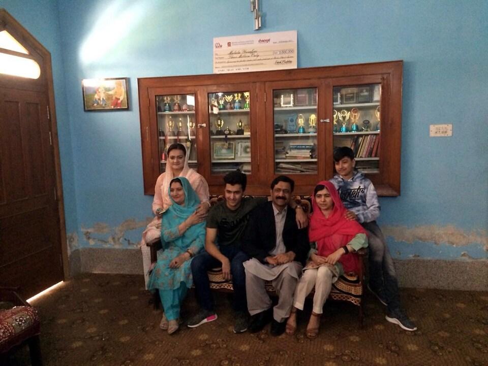 Malala et cinq membres de sa famille sont assis sur le canapé familial, devant une étagère remplie de trophées.