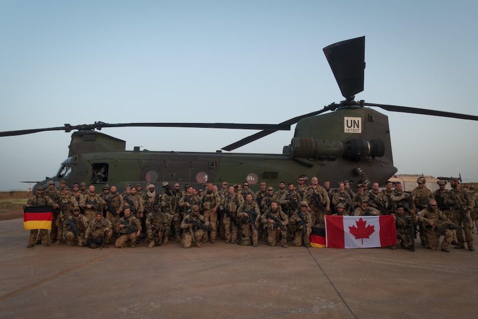 Des soldats avec des drapeaux allemands et canadiens devant un Chinook.