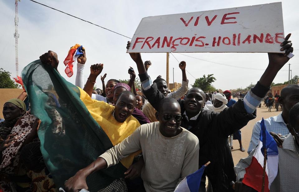Des Maliens sourient et crient dans la rue. L'un d'eux tient une pancarte sur laquelle il est écrit : «Vive François Hollande».