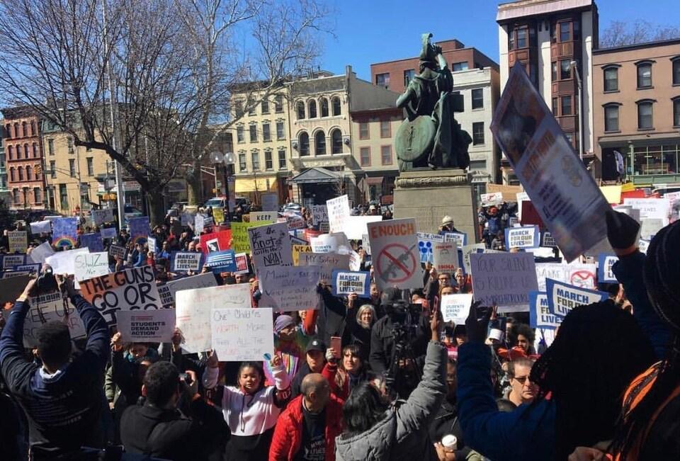 La foule brandit des pancartes.