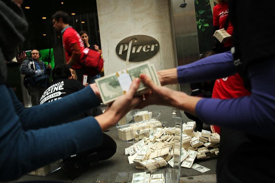 Des manifestants empilent des centaines de faux billets de banque devant l'entrée de Pfizer.