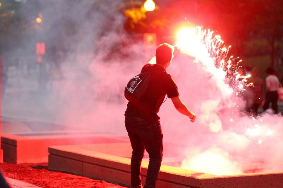 Vue de dos d'un manifestant qui agite un feu de détresse.