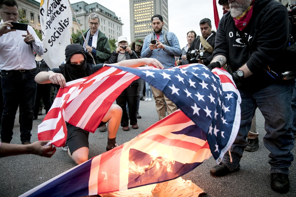 Des manifestants enflamment un drapeau américain et un drapeau britannique.