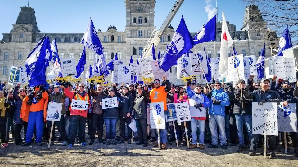 Des manifestants, pancartes en main et poing levé, se tiennent devant l'Assemblée nationale du Québec.