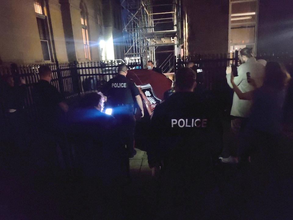 Les policiers transportent une tente et se dirige vers une zone fermée par une clôture de métal.