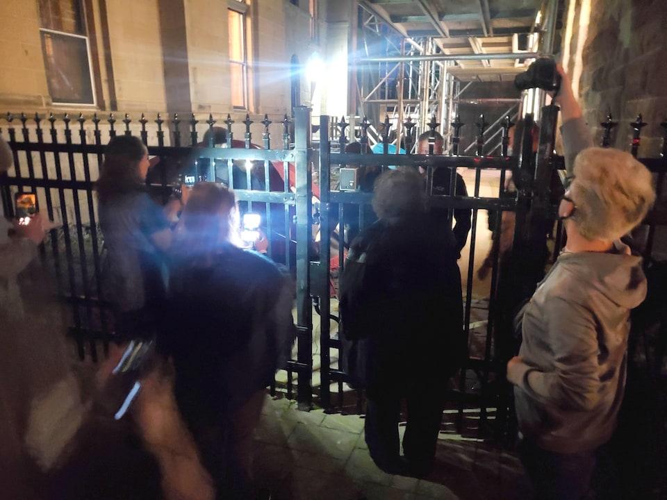 Groupe de femmes devant une clôture de métal fermée. Derrière la clôture, des policiers et les effets qu'ils ont confisqué aux manifestants.