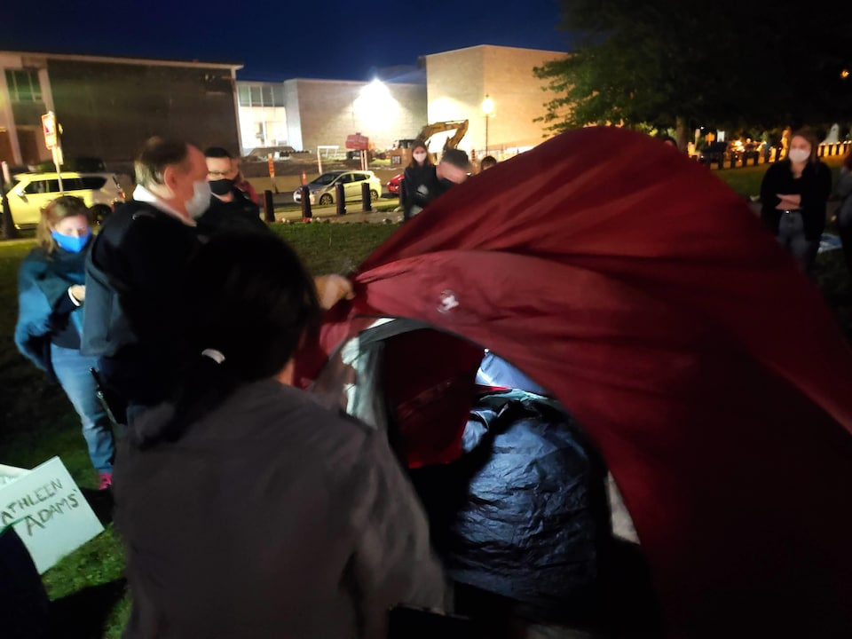 Un agent de police agrippe une tente posée sur le gazon.