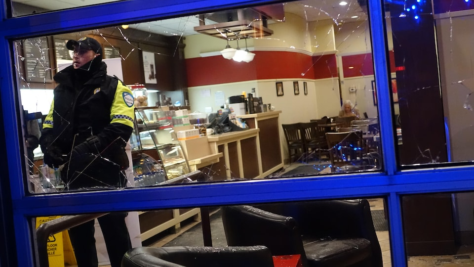Une vitre brisée montre l'intérieur d'un café, une dame est assise au fond de l'établissement.