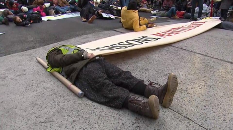 Un manifestant est couché sur le dos sur l'asphalte afin de simuler la mort pendant une marche pour le climat.
