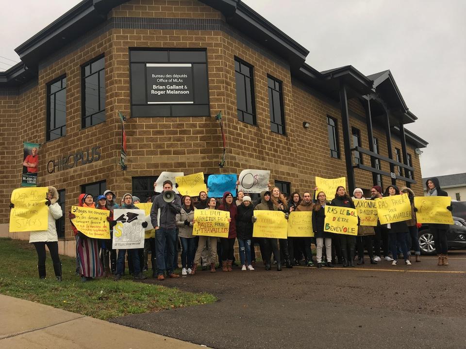 Des étudiants avec des pancartes manifestent devant les bureaux du premier ministre Brian Gallant et du ministre de l'Éducation postsecondaire, Roger Melanson.