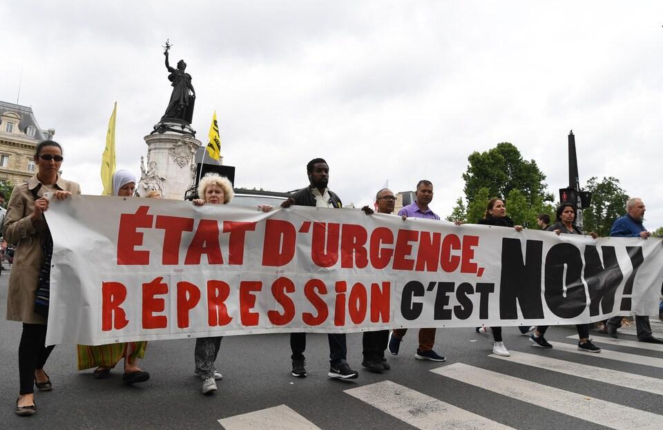 Des manifestants tiennent une pancarte disant «état d'urgence, répression, c'est non»