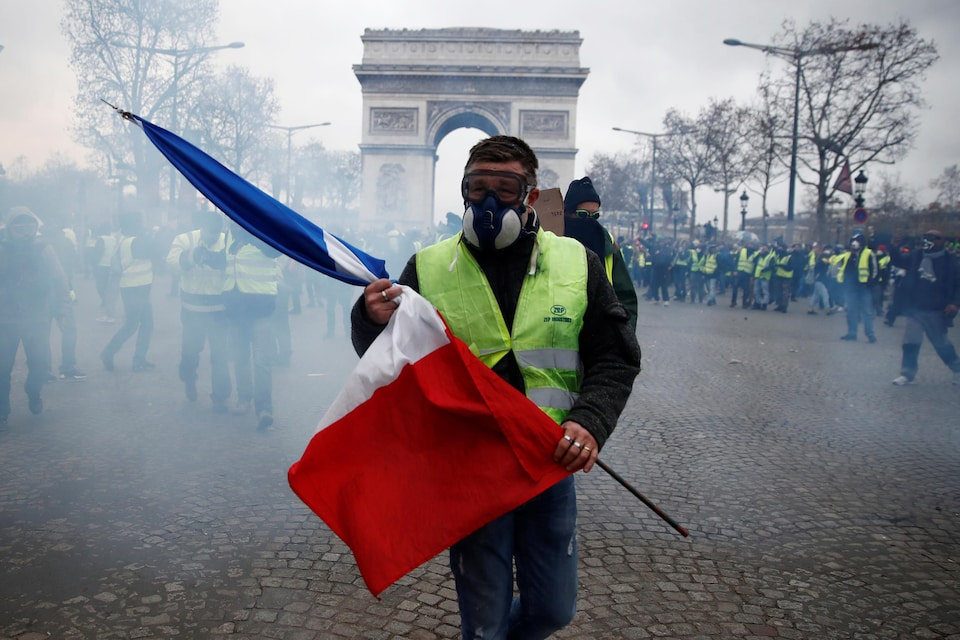 "A protester wearing a yellow vest holds a French flag as he walks among tear gas on the Champs-Elysees Avenue near the Arc de Triomphe during a national day of protest by the ""yellow vests"" movement in Paris, France, December 8, 2018.  REUTERS/Christian Hartmann - RC17656D3B00"