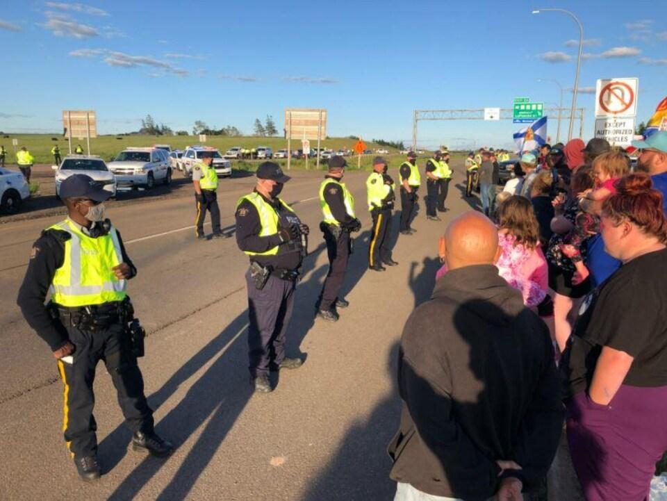 Des policiers forment un rang devant des dizaines de manifestants.