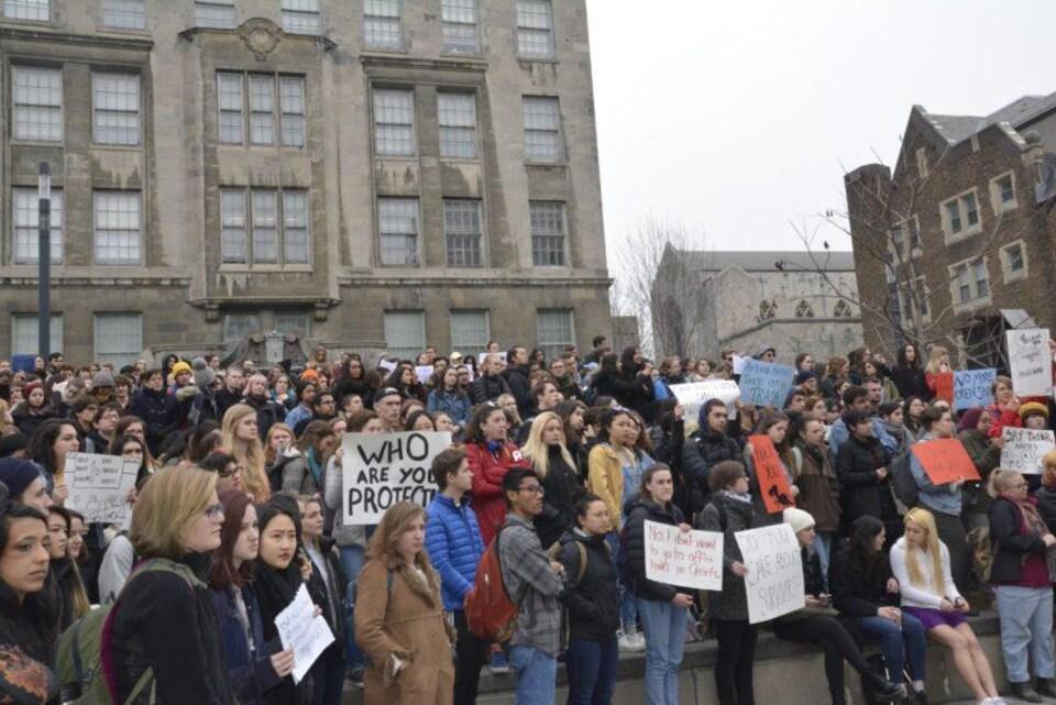 Un grand groupe d'étudiants qui participent à une manifestation sur le campus de l'université McGill.