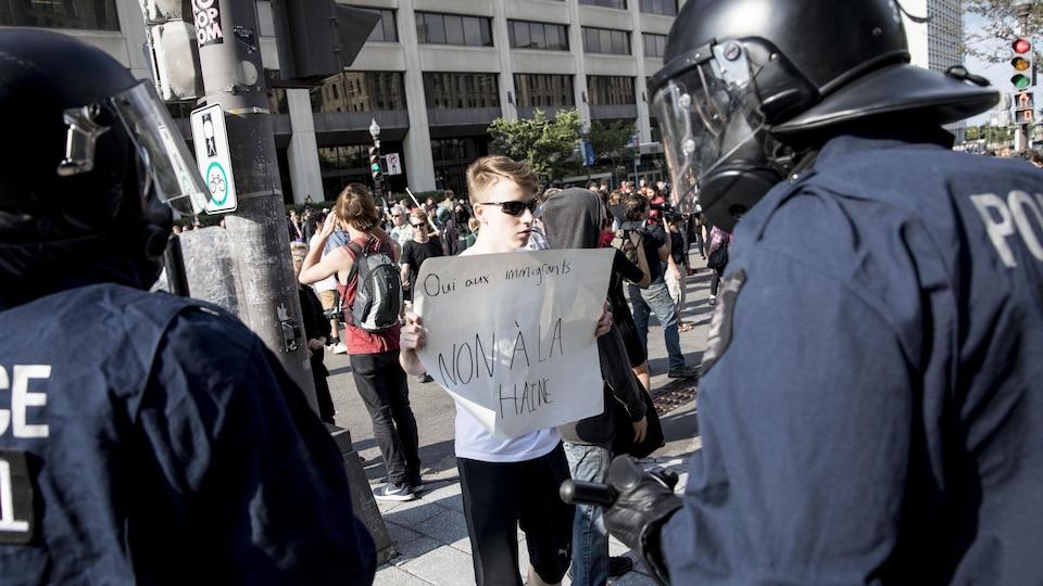 Un homme refuse de reculer malgré les avertissements des policiers.