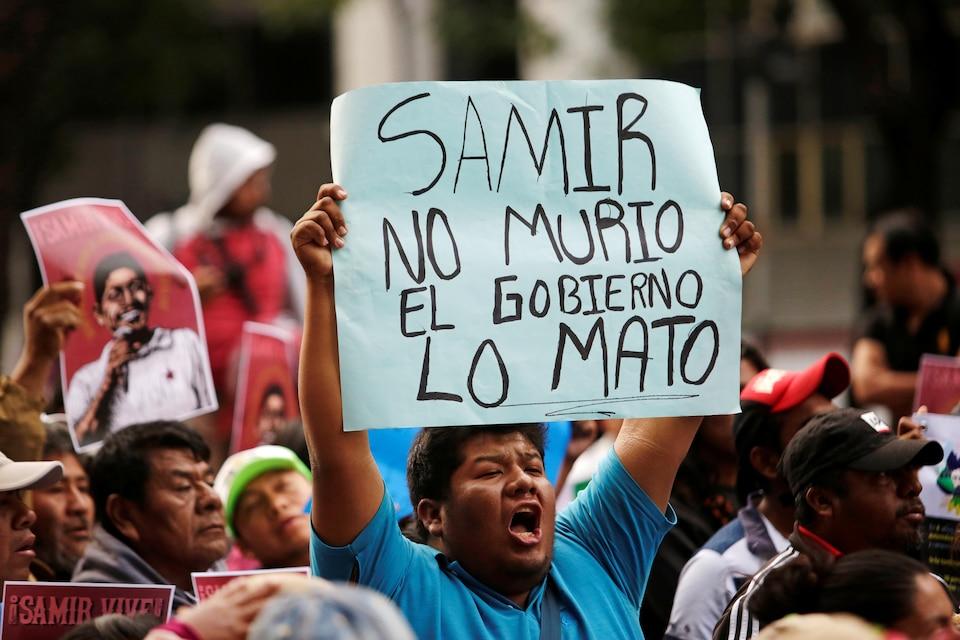 Un homme parmi la foule brandit une pancarte sur laquelle est écrit «Samir n'est pas mort; le gouvernement l'a tué».