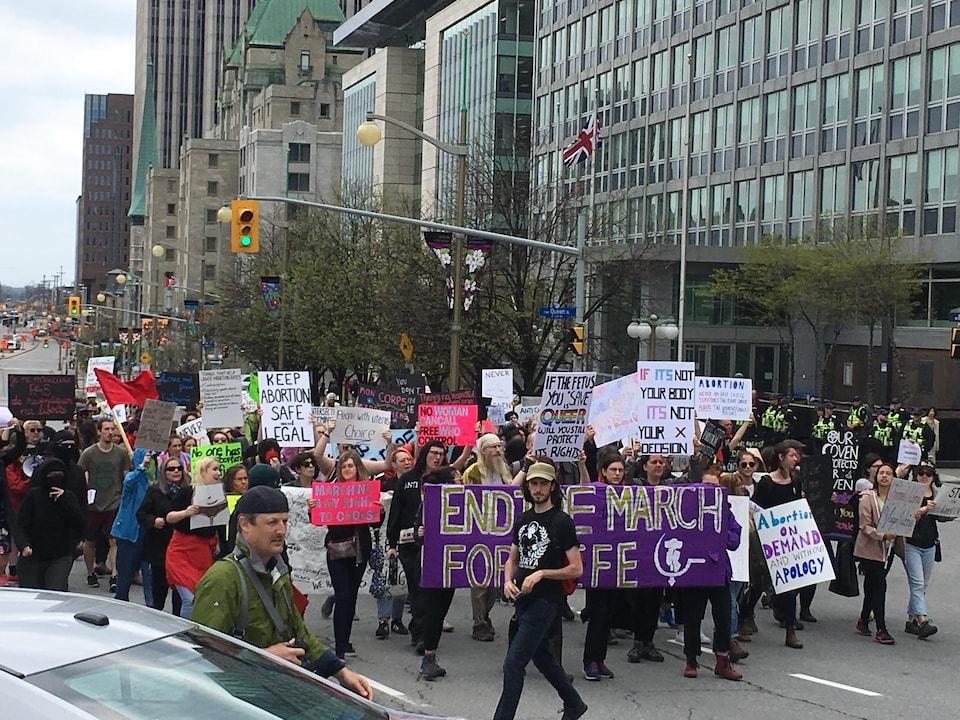 Des manifestants pro-choix dans la rue à Ottawa. On peut voir une banderole où on peut lire «Arrêtez la marche pour la vie».