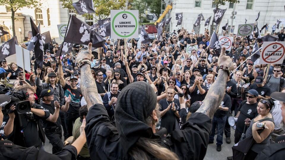 Un homme, pouces levés, s'adresse à la foule composée de membres du groupe La Meute, venus manifester contre «l'immigration illégale», à Québec.