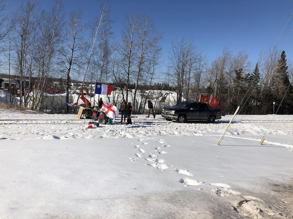 Campement près d'une voie ferrée enneigée.