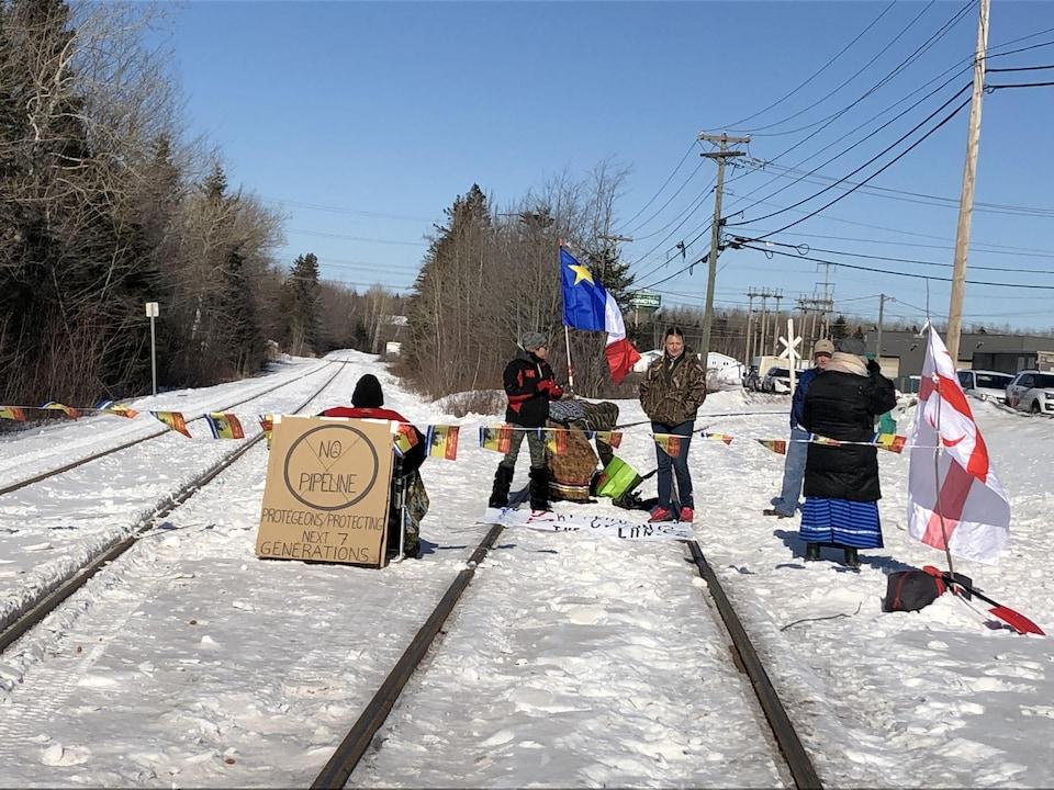 Manifestants réunis sur une voie ferrée en hiver.