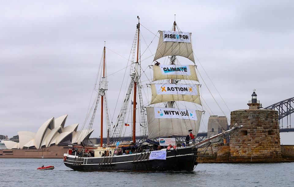 Une goélette avec des banderoles dénonçant les changements climatiques devant l'opéra de Sydney