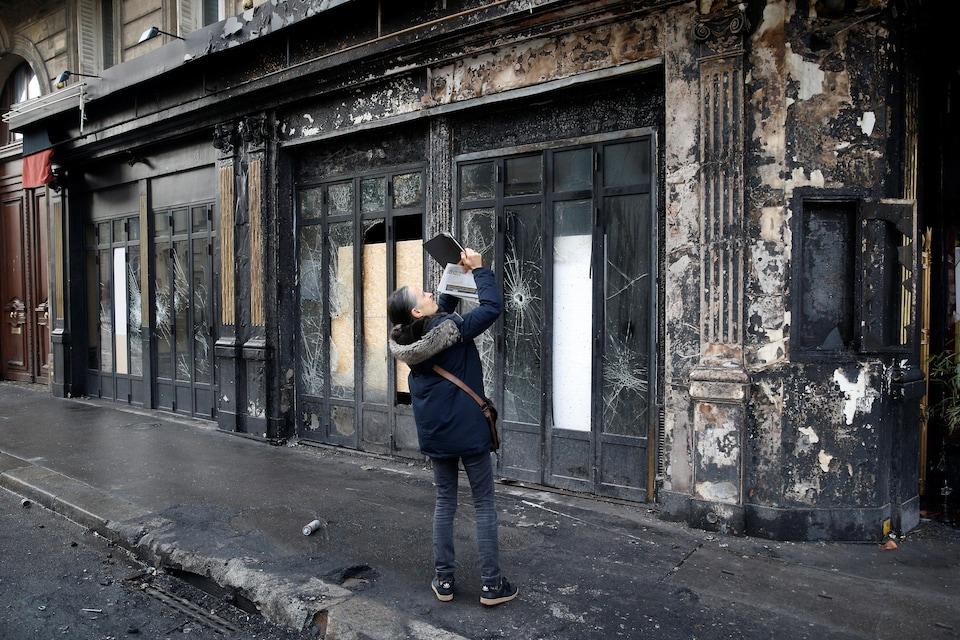 Une femme prend en photo la façade d'un restaurant incendié.