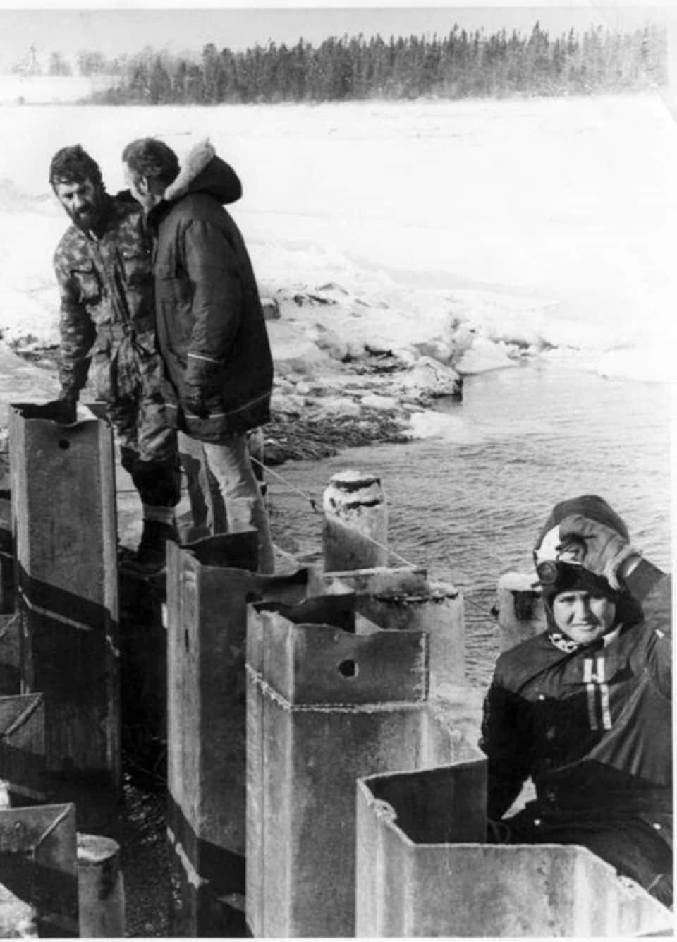 Trois personnes se trouvent sur le petit barrage métallique.