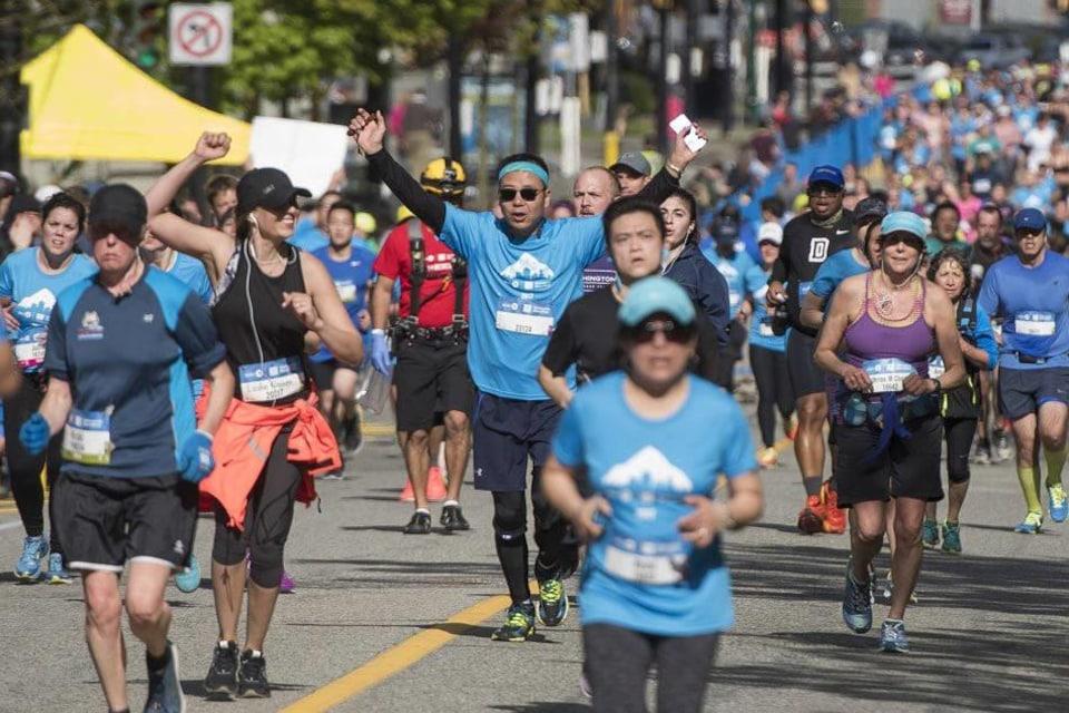 Deux coureurs les bras levés terminent un marathon à Vancouver avec une foule d'athlètes autour.