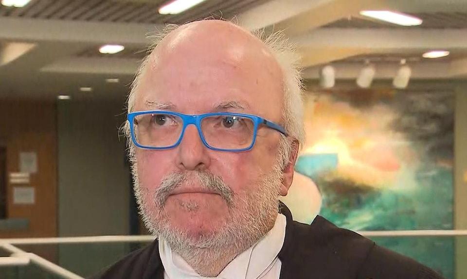 L'avocat est un homme chauve avec une barbe courte et des lunettes bleues.
