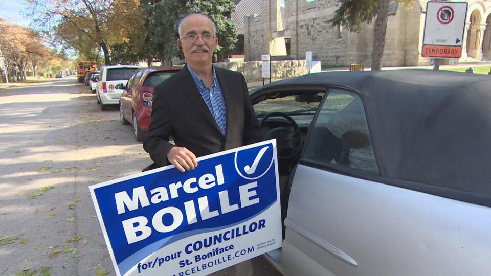 Un homme sort de sa voiture et tient une pancarte électorale qui dit «Marcel Boille for/pour Councillor- St. Boniface».