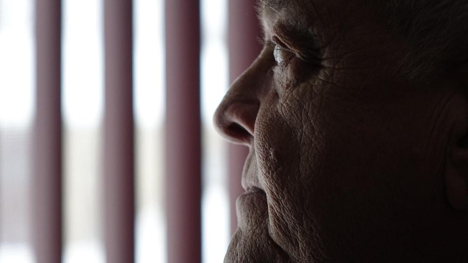 Marcel Bolduc qui regarde à la fenêtre.