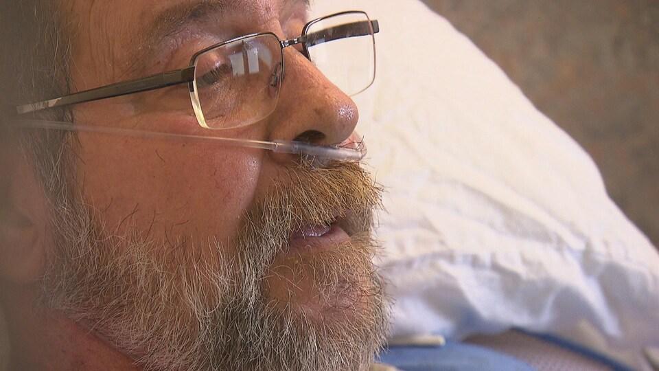 Visage d'un homme portant la barbe et des lunettes en entrevue dans sa chambre d'hôpital.