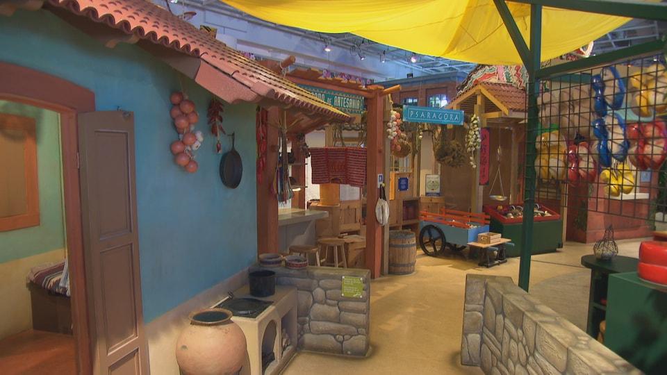 Un espace de jeu coloré et aménagé pour rappeler un marché d'alimentation dans un musée pour enfants.