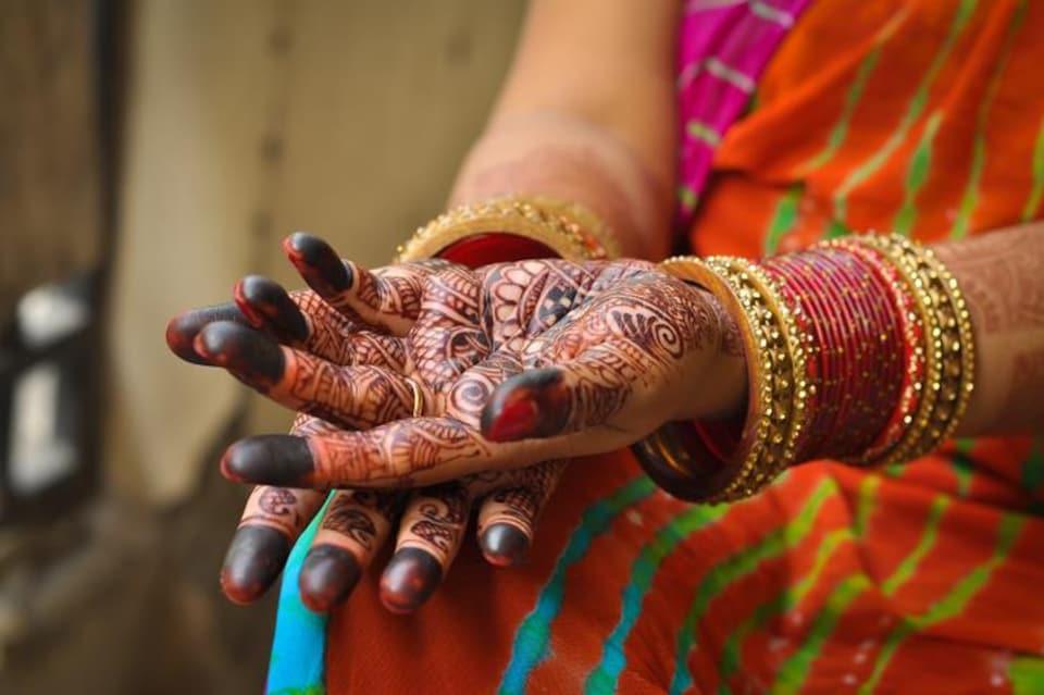 Selon la coutume, les mains de la mariée sont décorées avec du henné.