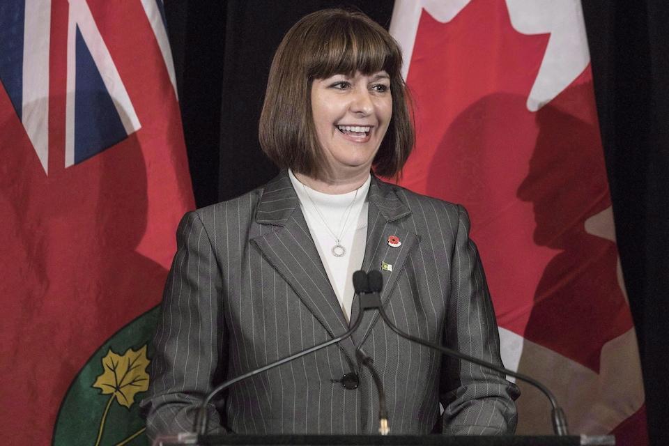 La députée libérale Marie-France Lalonde au podium devant les drapeaux ontarien et canadien