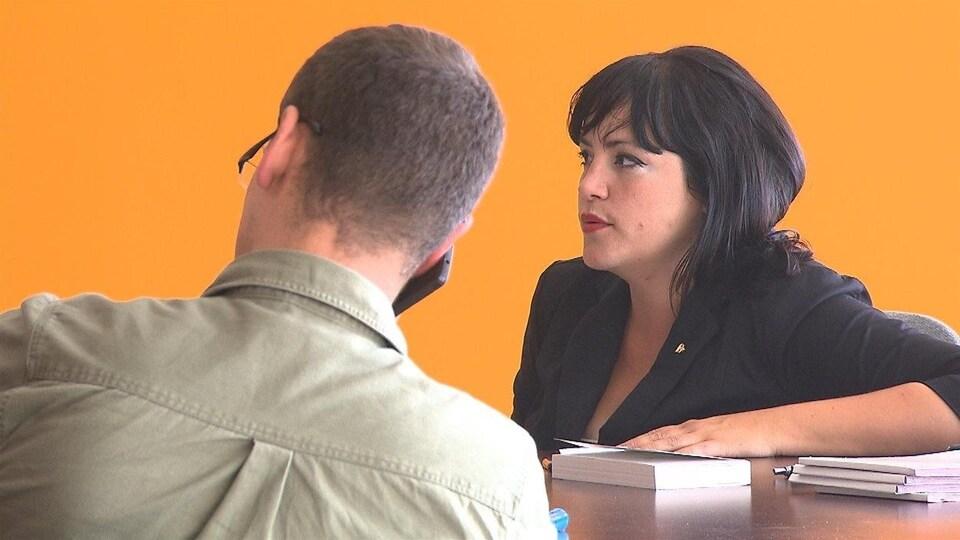Marilène Gill est assise et écoute une conversation