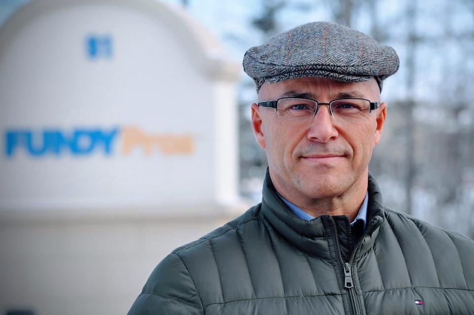 Mario Allain, devant l'affiche de son entreprise au Nouveau-Brunswick.