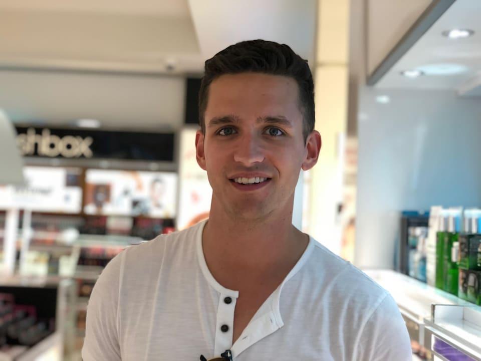 Un jeune homme dans un magasin de produits cosmétiques.