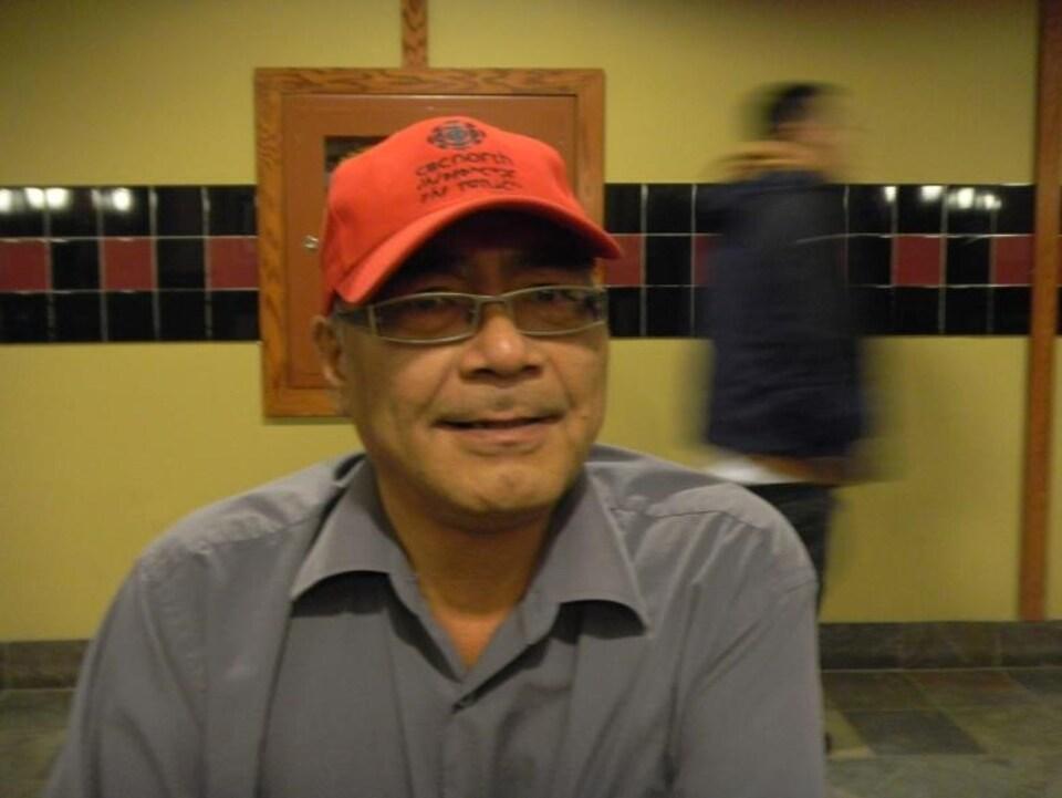 Un homme avec une casquette orange et des lunettes.