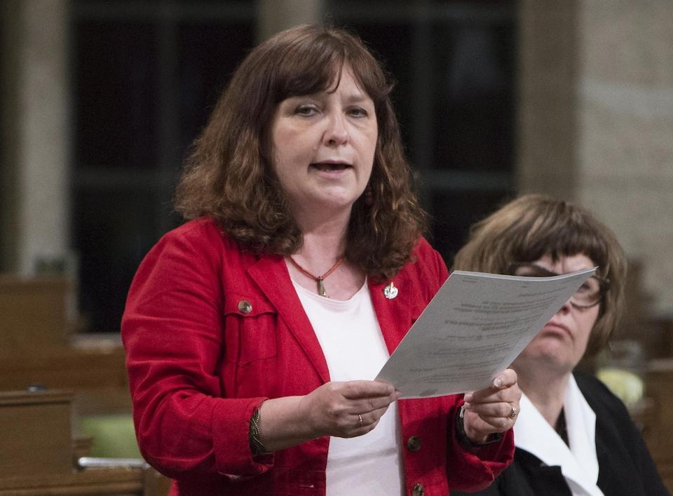 Une femme tient une liasse de papiers et regarde devant elle dans la Chambre des communes.
