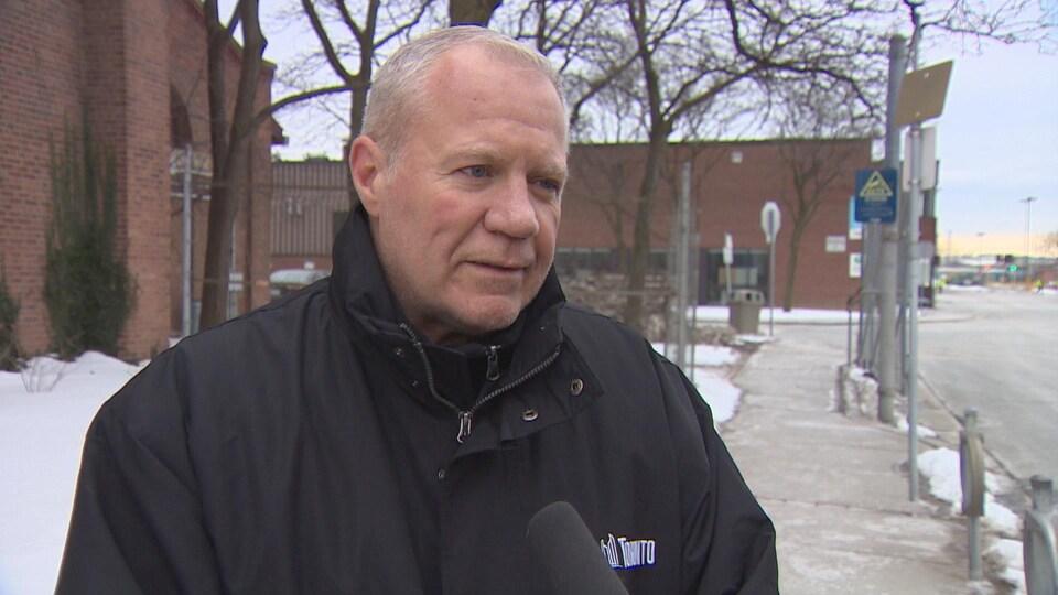 Mark Mills, surintendant municipal, est dehors, a les cheveux courts et blanc, il a les yeux bleus, il porte un manteau noir avec le logo de la Ville de Toronto et il parle au micro de Radio-Canada