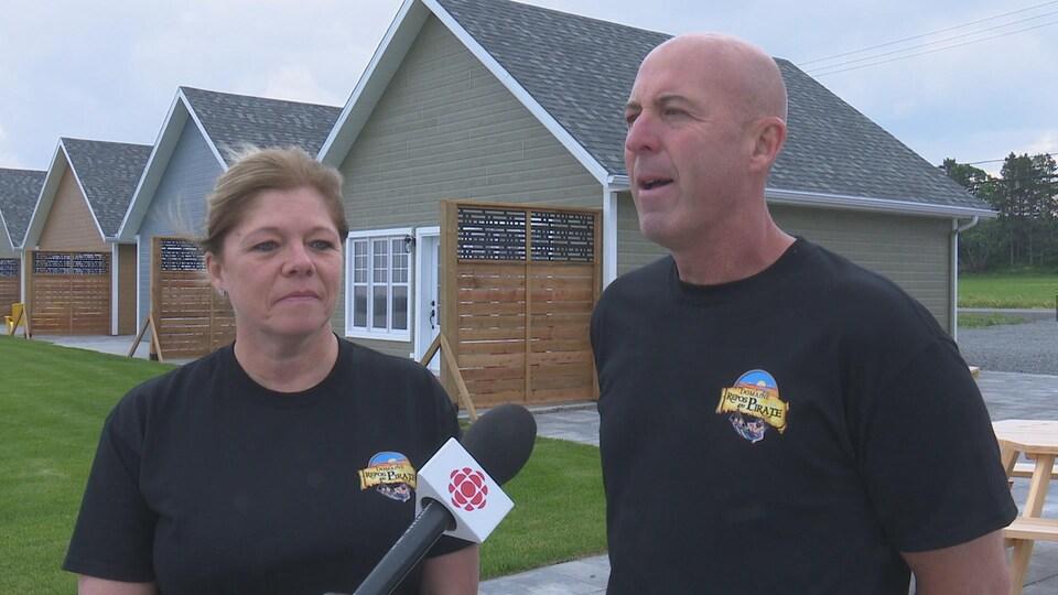 Une femme et un homme se font interviewer devant des petites maisons au Domaine du Repos.